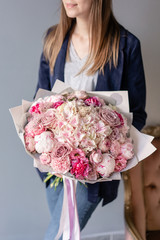 Pink peonies and hydrangea. Beautiful bouquet of mixed flowers in woman hand. Floral shop concept . Handsome fresh bouquet. Flowers delivery. Red and pink color.
