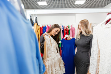 Happy young woman choosing clothes in mall or clothing store
