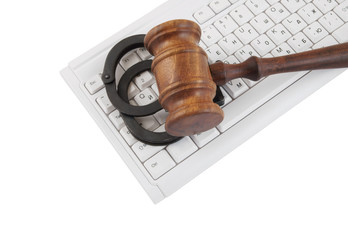 Gavel and handcuffs on white computer keyboard isolated on white