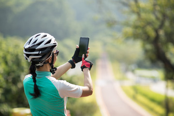 Taking pictures with smartphone while riding bike on sunny day