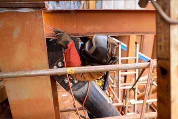 Wide angle pic of maintenance welder wearing safety red glove welding helmet with power air purifying respirator while performing welding a difficult task condition to protect from the toxic fume