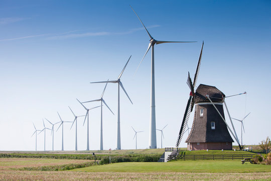 old dutch windmill and modern wind turbines against blue sky in dutch province of groningen