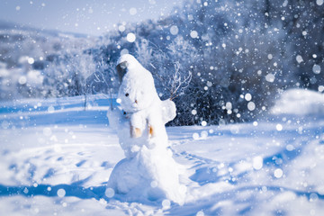Snowman on a winter day against the background of the forest and snow