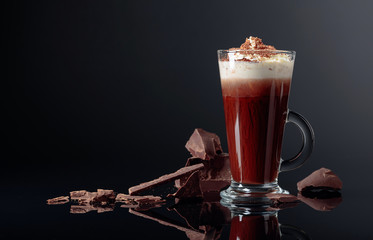 Hot chocolate with whipped cream and pieces of dark chocolate on a black background.
