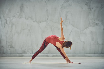 Attractive brunette in red sportswear barefoot doing Triangle yoga posture.