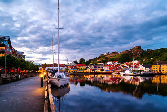 View of the illuminated houses and yachts with Fredriksted fortress at the background in Halden, Norway