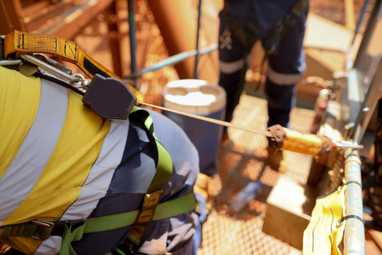 Worker on Elevating Work Platform  wearing fall arrest safety harness using retraceable device clipping with Karabiner  attached on the back of harness loop other end attached with anchorage basket