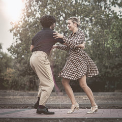 Swing dancers couple stepping outdoors in the park. Vintage filtered image
