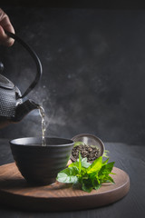 Pour hot tea with steam into cup on black table. Chinese tea.