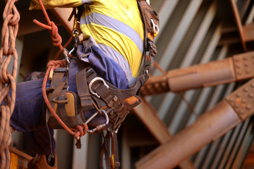 Closeup picture of male rope access inspector worker wearing full safety harness setting on a chair, abseiling performing wall leaking inspection working at height construction site, Sydney, Australia
