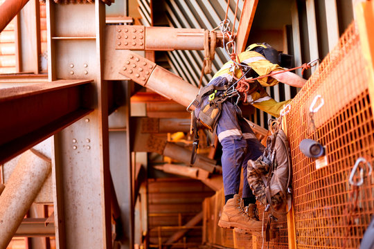Wide angle view picture of male rope access welder worker wearing full safety harness, helmet working hanging on tie line setting on a chair, abseiling working at height construction site, Sydney