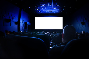 Cinema or theater in the auditorium. people watching a movie. Mockup with white blank screen