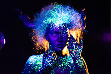 devil makeup and contact lenses. Woman in ultraviolet body painting. The girl is painted in fluorescent powder. Body art glowing in UV light. Stars in the eyes.