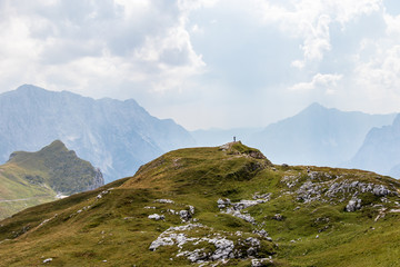 Man alone on Summit between huge Mountain Chains inside beautiful Nature. Summer Day Panorama. Julian Alps, Triglav National Park, Slovenia.