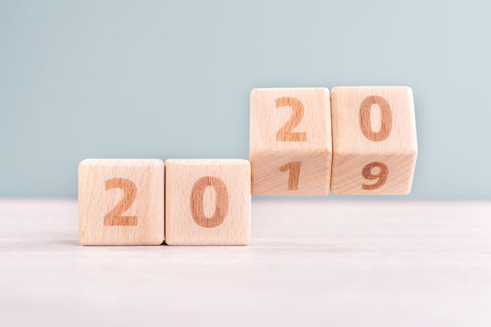 Abstract 2020 & 2019 New year countdown design concept - wood blocks cubes on wooden table and low saturation green background, close up, copy space.