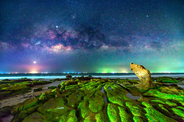 Night landscape with milky way and mossy rocks on the beach