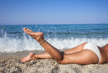 Close up outdoor shot of beautiful woman legs on the sea shore