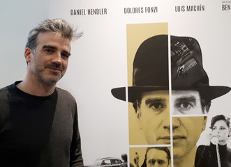 """Uruguayan actor Daniel Hendler poses for a picture in front of the poster of """"The Moneychanger"""" film in Buenos Aires"""