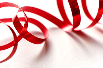 Red curly ribbon on white background. Abstract image of serpentine with curls for use as a christmas, anniversary, valentine or celebration background with copy space.