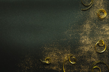 Golden sparkles and ribbons on black background. Festive concept. - Image