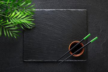Chopsticks and bamboo bowl on black rock slate plate