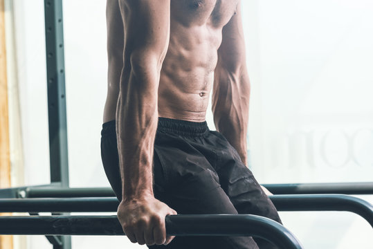 Muscular young man exercising at the gym