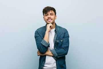 Young hispanic cool man smiling happy and confident, touching chin with hand.