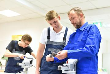 Berufsausbildung im Handwerk - Ausbilder und Lehrling in der mechanischen Werkstatt