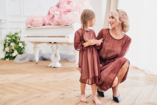 Charming smiling luxurious mother and pretty daughter