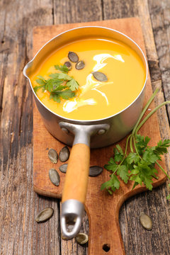 bowl of pumpkin soup in pan with cream on wooden board