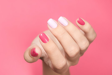 Photo sur Aluminium Manicure Closeup view of single beautiful white hand of caucasian adult woman with trendy asymmetric two colours bright manicure isolated on pink background. Horizontal color photography.