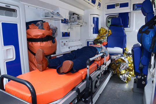 Interior of an ambulance car: dummy lying on a stretcher, bags, medical equipment