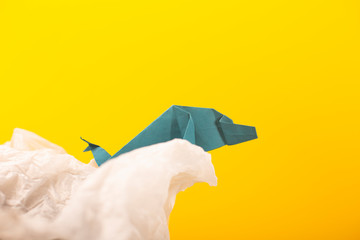 whale on a wave handmade origami craft paper art on a yellow paper background