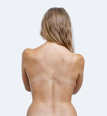 Woman with brown hair turned her bare back to the camera on a white background.