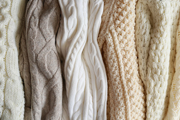 Bunch of knitted warm pastel color sweaters with different vertical knitting patterns hanging in...