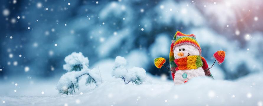 little snowman on soft snow on blue background