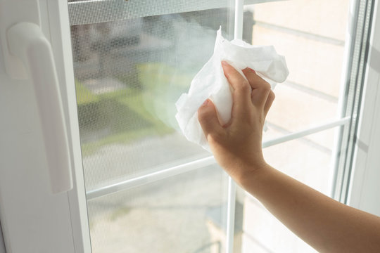Child hand cleaning window with white rag