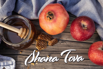 Jewish National Holiday. Rosh Hashana with honey, apple and pomegranate on wooden table.