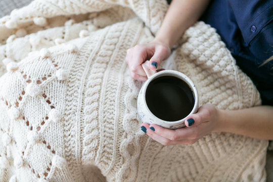 Girl holding cup of coffee in bed with white knitted blanket, cozy morning