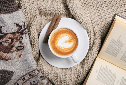 Cup of coffee, book, warm socks and beige knitted sweater, top view. Winter drink