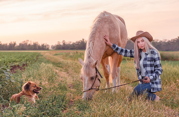 young blonde girl dressed in a cowboy hat and blue jeans with a beige horse and a dog on the ranch