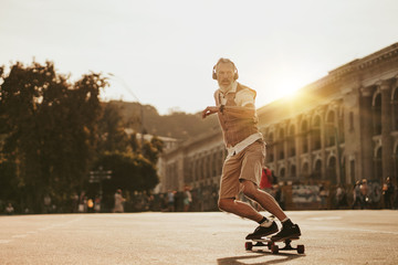 Portrait of handsome man in white shirt on sunset evening in summer. Stylish guy ride on skateboard on city street. Urban male lifestyle on buildings background