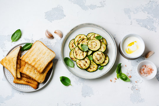 Grilled zucchini salad with basil leaves, yogurt sauce and fried bread in a simple ceramic plate on a white concrete background. Flat lay with copy space.