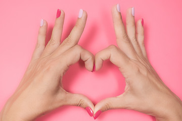 Closeup top view of beautiful female hands with modern trendy multicolor manicure isolated on pink background. Woman making heart gesture with 2 hands. Love and family concept.