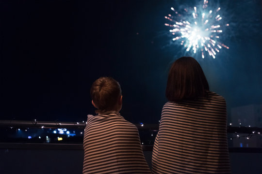 Mother and son looking at New Year celebration fireworks in night sky warmly wrapped in striped plaids standing on home balcony.