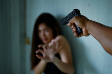 Hand of man and threatening with gun to frightened young woman. Criminal and robbery for woman concept. Violence against Women concepts.