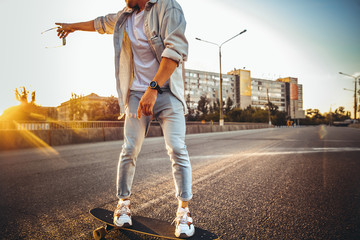Young caucasian man riding on longboard or skateboard, modern shot in film grain effect and vintage style. Sunset in summer evening. City's street. Toned in teal orange. Looks confident and cool.