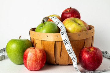 red and green apples in a basket with measuring tape and white background