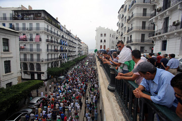 People watch demonstrators shouting slogans during a protest to reject the Algerian election announcement for December, in Algiers