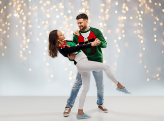 christmas, people and holidays concept - happy couple dancing at ugly sweater party over festive lights background